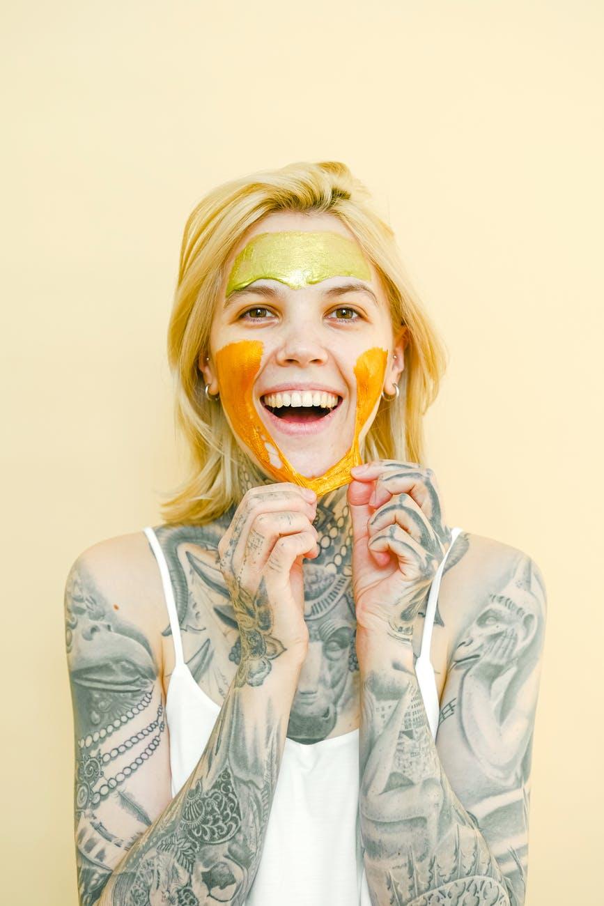 happy tattooed woman in peel off mask